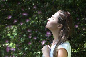 Achtsamkeit. Frau hält das Gesicht in der Natur in die Sonne.