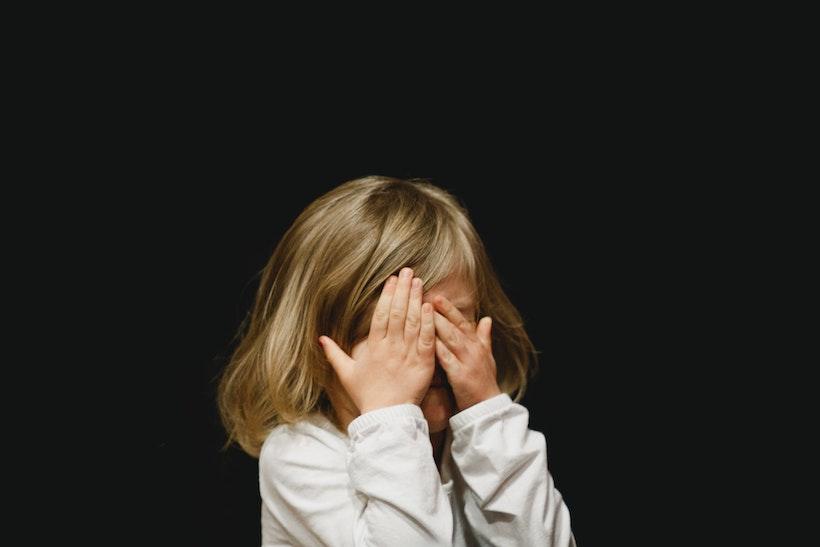 Mädchen hält sich die Augen zu und hat Angst