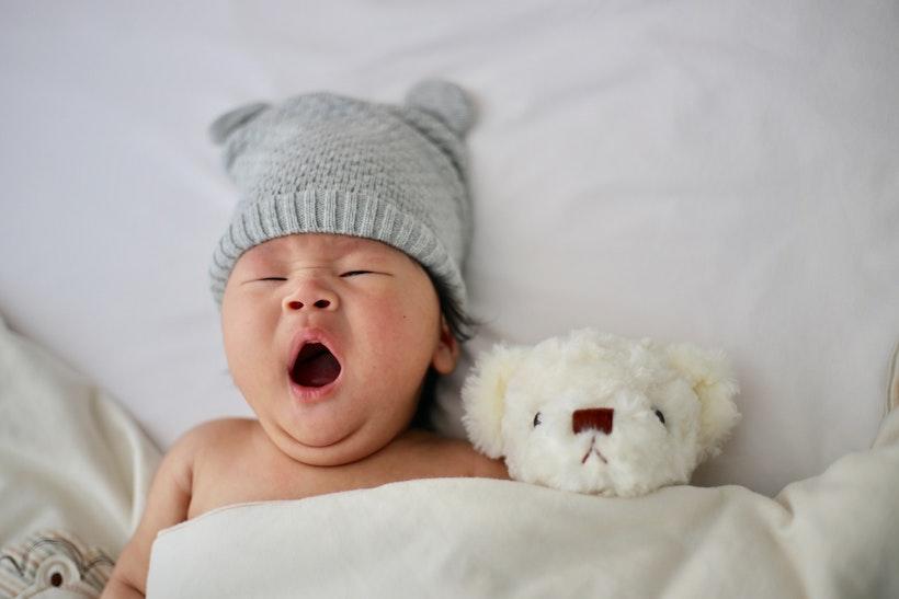 Gähnendes Baby im Bett mit Mütze und Teddy