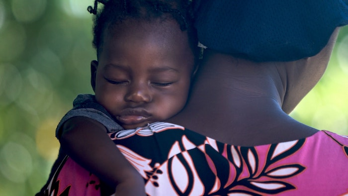 Mutter trägt schlafendes Baby auf dem Arm